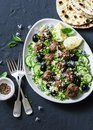Salad with lamb meatballs, avocado, greek yogurt sauce, couscous and whole grain flatbread on a dark background, top view. Royalty Free Stock Photo