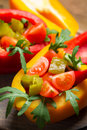 Salad made of fresh vegetables and served in peppers on old wooden table Royalty Free Stock Photo