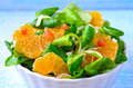 Salad with oranges and lamb s lettuces white bowl of on a blue background Stock Image