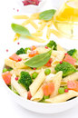 Salad with pasta smoked salmon and vegetables broccoli green peas ingredients in the background isolated on a white background Stock Photo