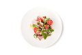 Salad with smoked ham and arugula in the white ceramic plate Royalty Free Stock Photo