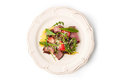 Salad with smoked ham and arugula in the white plate top view Royalty Free Stock Photo
