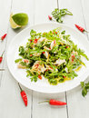 Salad with steamed sea bass fillet chili pepper rucola cilantro and ginger in olive and linseed oil shallow dof Royalty Free Stock Photo