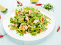 Salad with steamed sea bass fillet chili pepper rucola cilantro and ginger in olive and linseed oil shallow dof Stock Photo
