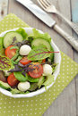 Salad with tomato and mozzarella cheese mix different kinds of leaves in bowl on wooden background Royalty Free Stock Photo