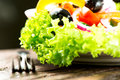 Salad with vegetables and greens in plate with fork close up on wooden table Royalty Free Stock Photography