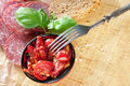 Salami and dried tomatoes sun sliced bread basil on a wooden table Royalty Free Stock Photo