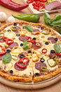 Salami and vegetable pizza with ingredients peppers olives in the back Royalty Free Stock Images
