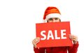 Sale announcement pretty girl in santa cap announcing Royalty Free Stock Photos