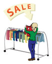 Sale a girl next to colorful rack of clothes on Stock Image