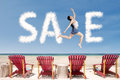 Sale promotion concept clouds and woman jumping over beach chair Stock Photos