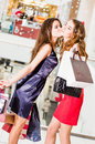 Sale,  shopping and happy people concept - two beautiful women with shopping bags.girl kissing girlfriend Royalty Free Stock Photo