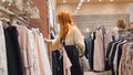 Sale - woman in dress store chooses a clothes - shopping concept Royalty Free Stock Photo