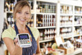 Sales assistant in food store handing credit card machine to cus portrait of customer Royalty Free Stock Photography
