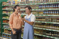 Sales clerk assisting women examining jar in the supermarket beijing Stock Photography