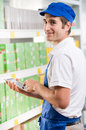 Sales clerk with tablet young holding a digital and working at supermarket Royalty Free Stock Photos