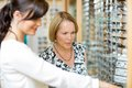 Salesgirl assisting woman in selecting glasses senior women at optician store Stock Photos
