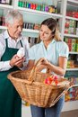 Salesman assisting customer buying groceries senior female in supermarket Stock Photo