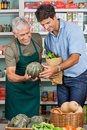 Salesman assisting male customer happy senior in shopping vegetables at supermarket Stock Images