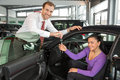 Salesman in car dealership sells automobile to customer a happy and hands over the keys Royalty Free Stock Images