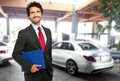 Salesman in a car showroom smiling Royalty Free Stock Images