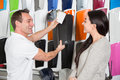 Salesman consulting a customer about car wrapping foils in different colors Royalty Free Stock Photography