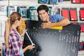 Salesman with customer examining wrench size using portrait of confident female board in hardware store Stock Photos