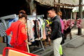 Salesman helps two women customers find the right size in front of his clothing shop on the main street in jiu chi town sichuan Stock Photography