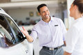 Salesman selling car friendly to a customer in showroom Royalty Free Stock Photo