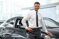 Salesman stands near brand new car car showroom Stock Photos