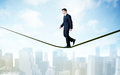 Salesman walking on rope above the city Royalty Free Stock Photo