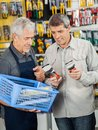 Salesperson assisting customer in buying pliers senior at hardware store Royalty Free Stock Photos