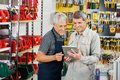Salesperson and customer using tablet computer in hardware store Royalty Free Stock Photography