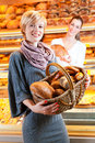 Salesperson with female customer in bakery baker or saleswoman her a and fresh pastries or products Stock Images