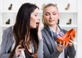 Salesperson offers stylish pumps for the customer female in shopping center Royalty Free Stock Photos
