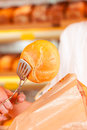 Salesperson is packing bread in bakery a for a customer a bag close up Royalty Free Stock Image
