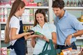Saleswoman assisting couple in buying groceries at supermarket Royalty Free Stock Photos