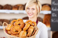 Saleswoman in bakery showing various bread loafs a basket Stock Images