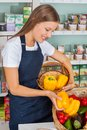 Saleswoman choosing bellpeppers in store young grocery Royalty Free Stock Photo