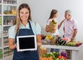 Saleswoman displaying tablet with customers in portrait of digital father and daughter communicating background Royalty Free Stock Image