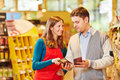 Saleswoman giving advice to man in supermarket men for buying chocolate Royalty Free Stock Photo