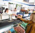 Saleswoman giving meat package to female customer happy at counter in butcher s shop Stock Image