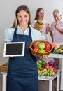 Saleswoman holding digital tablet and fruits portrait of basket with people shopping in background Royalty Free Stock Image