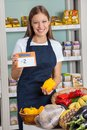 Saleswoman holding pricetag and bellpepper in portrait of young supermarket Royalty Free Stock Photography
