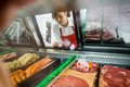 Saleswoman looking at variety of meat displayed in view young butcher s shop Stock Photos
