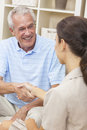 Saleswoman Shaking Hands With Senior Man at Home Royalty Free Stock Images