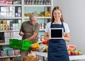 Saleswoman showing digital tablet while senior man portrait of men shopping in background Stock Photo