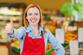 Saleswoman in supermarket holding thumbs up young happy her Royalty Free Stock Image