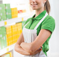 Saleswoman at supermarket young in uniform with arms crossed smiling Royalty Free Stock Photos