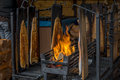 Salmon cooking and smoking on an open fire Royalty Free Stock Photo
